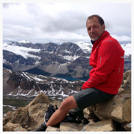 Jeff McSweeney, owner of Vantastic Rentals, resting on top of one of BC's Rocky Mountain peaks.