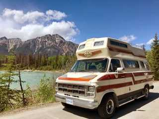 Camper Van rental parked beside a lake in the Rocky Mountains.